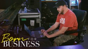 Chris working tech at a concert venue in a scene from Born For Business. Show logo in bottom left.
