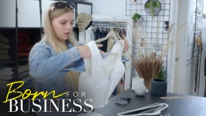 Lexi picking up a dress in a scene from Born For Business. Show logo in bottom left.