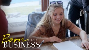 Lexi at a desk looking at a document smiling. Born for Business logo in bottom left.