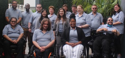 RespectAbility staff members smile together wearing gray polo shirts with the RespectAbility logo on them
