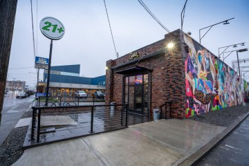 Zips Sodo Storefront, large brick building with glass doorway and graffiti side wall