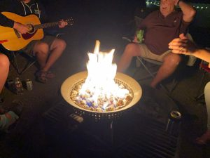 Kyle and Paul sitting around the campfire while Kyle plays his guitar