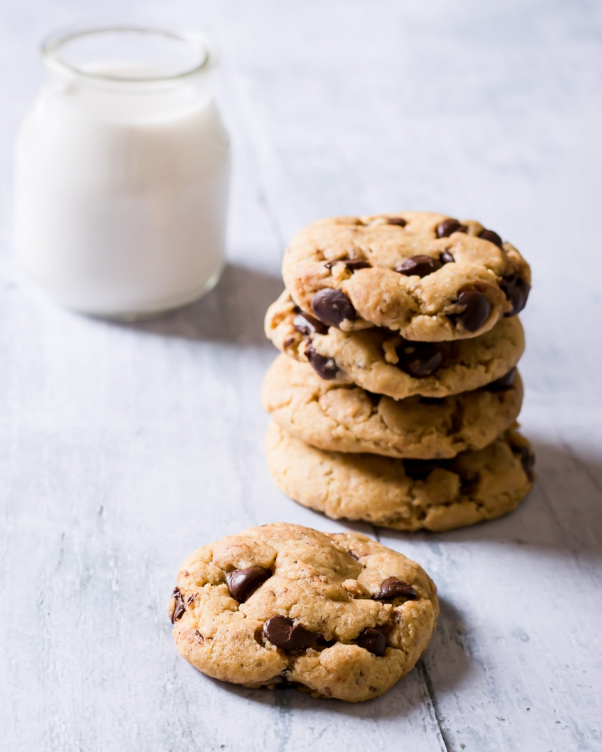 stack of chocolate chip cookies with glass of almond milk