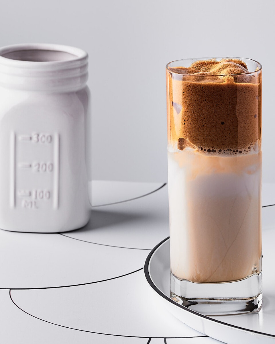 tall glass of vegan Dalgona coffee on a white round tray