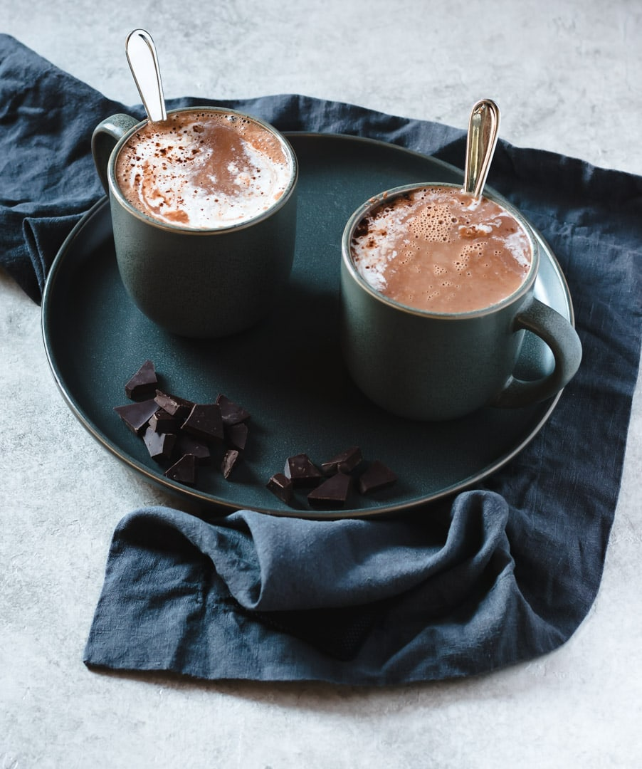 two mugs of hot cocoa on dark grey plate with chopped chocolate