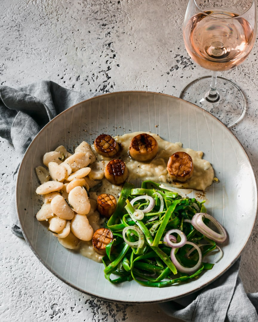 plate of king oyster mushroom scallops with shaved asparagus, lima bean butter, glass of wine