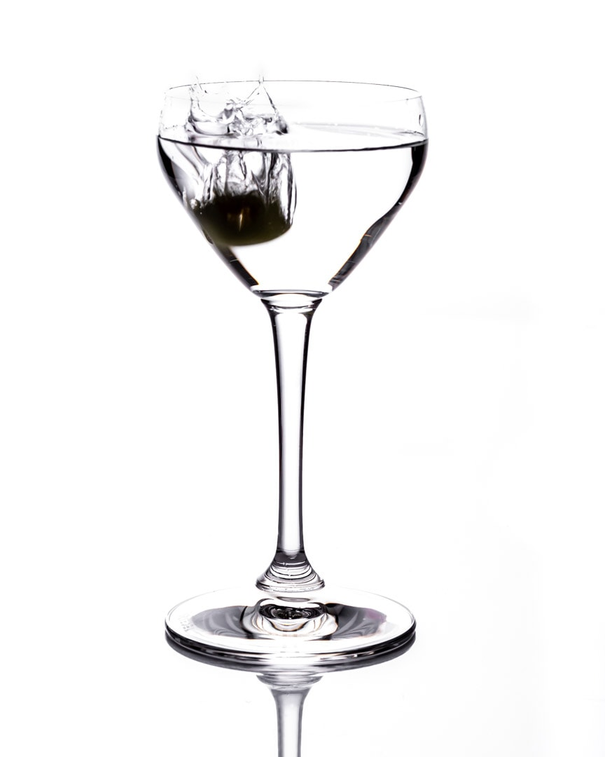 martini glass with olive dropped in white background