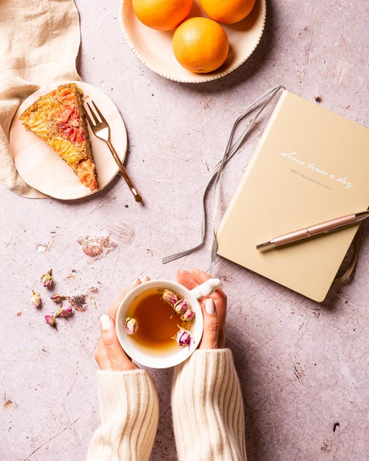 hands holding a cup of rosebud tea with diary and slice of blood orange cake