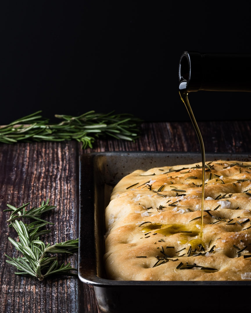 rosemary focaccia with olive oil being poured