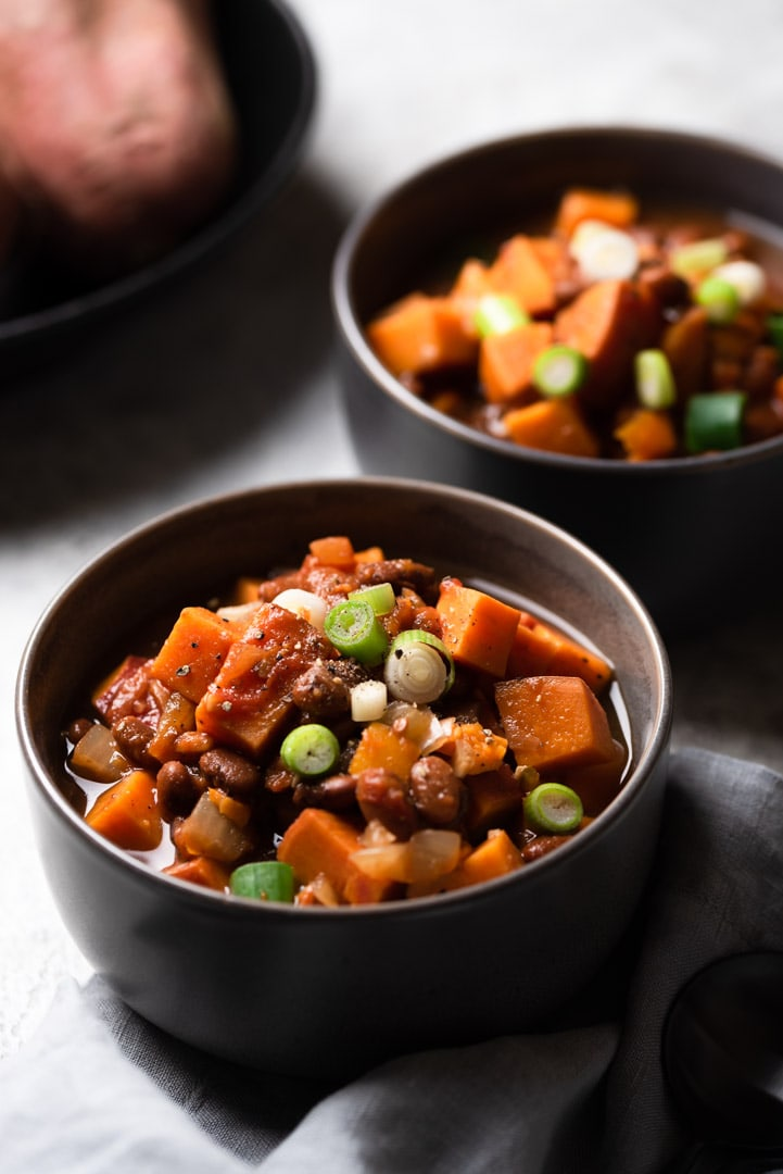 bowls of sweet potato bean stew in dark grey bowls