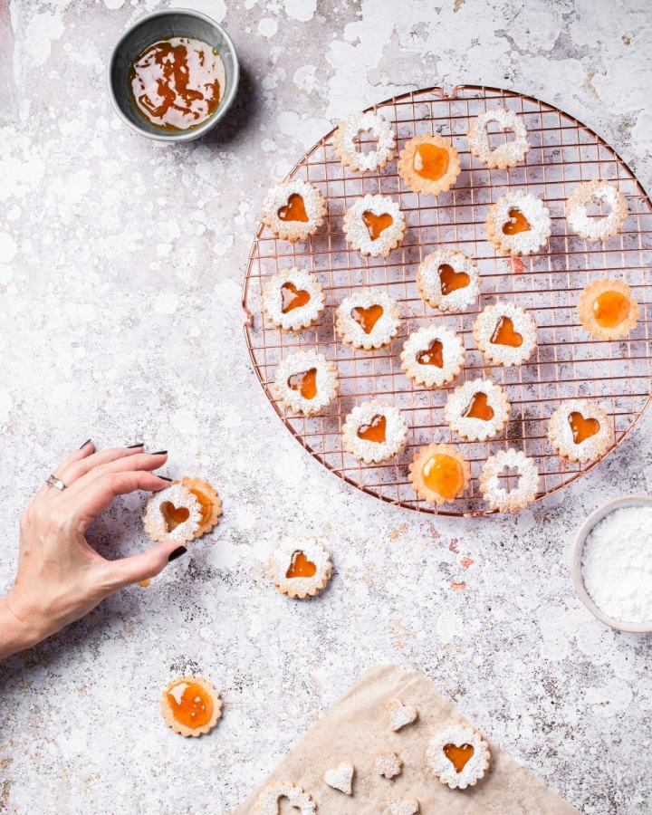 assembling vegan Linzer cookies with apricot preserves