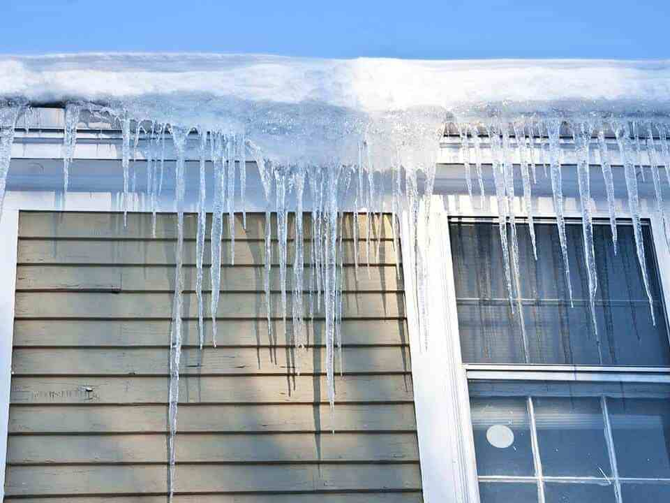 Ice Dam Hanging From Gutters of Home-min