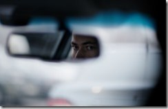 Man looking in the rear view mirror while driving