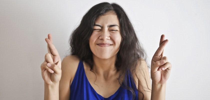 mulher fazendo figas com os dedos para saber como ganhar na Mega-Sena