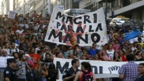 "Demonstrators march carrying a banner that reads ""Macri, stop"" to protest cuts in the public sector in Buenos Aires, Argentina, Jan. 29, 2016. 