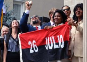 Cubans watch their flag being raised at the opening of the Cuban Embassy in Washington DC. Photo: Bill Hackwell