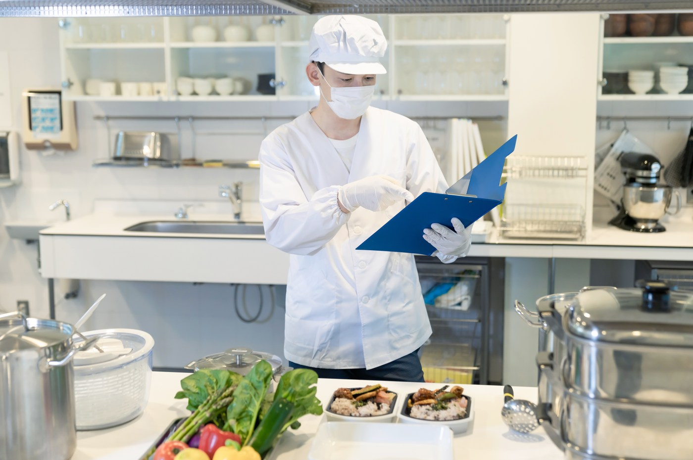 An Asian man in a white coat and hat wearing a white face mask and gloves points to something in a blue folder. He is in a mostly white kitchen, behind him is a sink, some dishes, and a stand mixer. In the foreground, there is a counter with raw vegetables, prepared rice with cooked toppings, hotel pans, a salad spinner, and a stockpot.