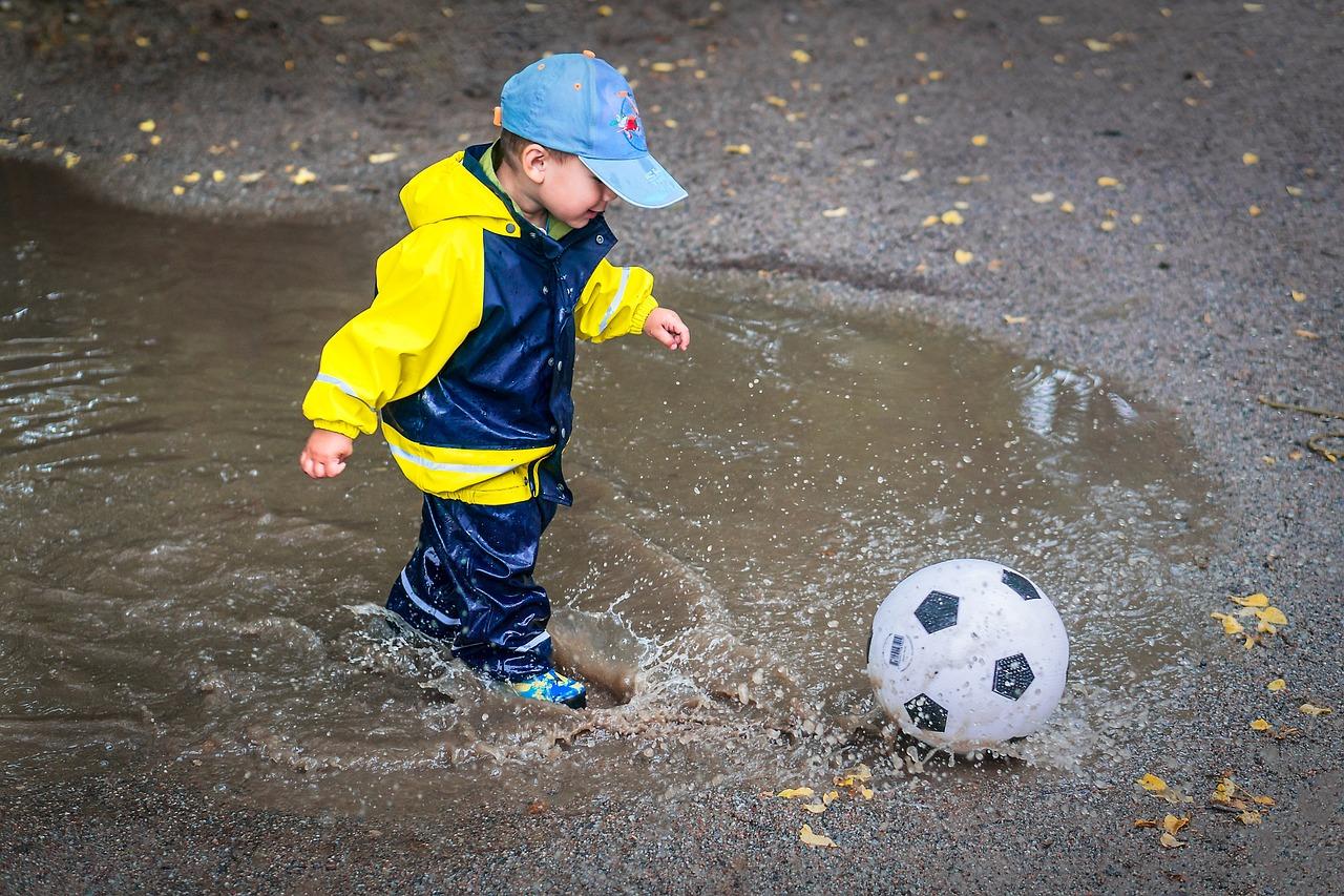 Spelend kind in regenpak en met voetbal