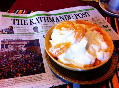 """Enjoying some juju dhau (""""King Curd"""") with fruit & muesli while reading the paper at Shiva Guesthouse in Bhaktapur."""