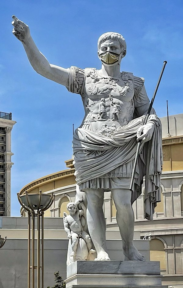 Caesar statue with face mask outside Caesars Palace on the Las Vegas Strip