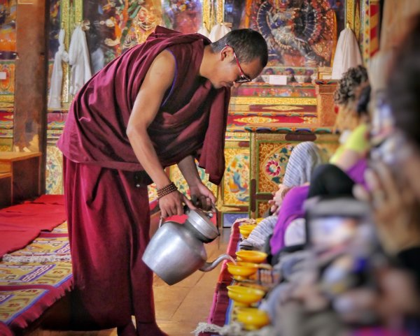 A monk pouring butter tea at Thiksey Monastery in Ladakh, india