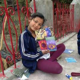 A girl posing with her collage art project outside Ramana's Garden Children's Home
