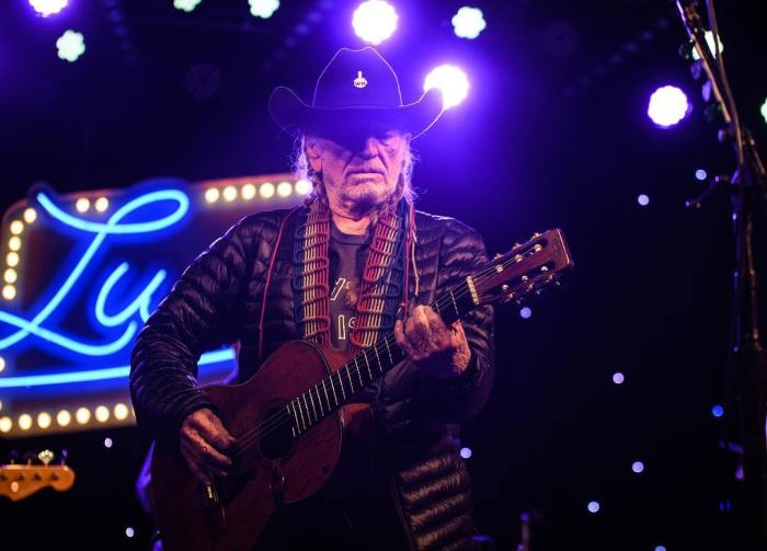 willie nelson performing guitar