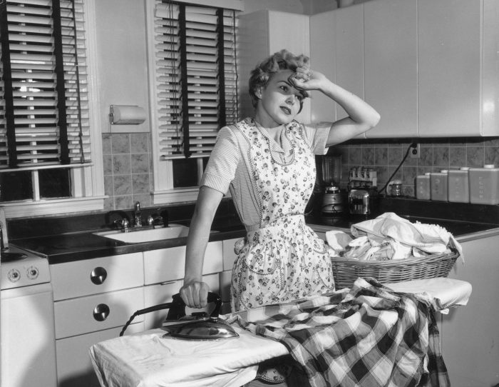 tired housewife in the 1950s ironing laundry