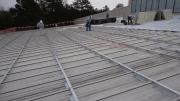 The roofing contractor elected to recover the building roof using specially fabricated steel sub-purlins, which permitted the installation of a new metal roof without removal of the old metal roof.