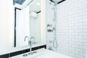Guest bathrooms have a New York City urban vibe with white subway tiles outlined along the perimeter with black tiles and concrete-like tile floors.