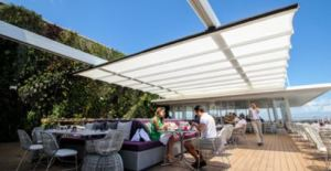 The En-Fold retractable fabric canopy system features pre-engineered components, creating a tensile structure that is built to withstand thunderstorm winds while in use.