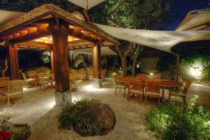 The outdoor courtyard includes a wooden pavilion ideal for outdoor dining, a rock fire feature, and pathways that lead to the beach.
