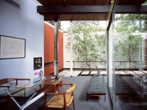 The extension of space created by the roof and floor planes continues beyond the glass walls.