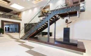 Originally one floor, the central entrance lobby was opened up to create a larger 2-story lobby with a grand staircase that connects to the hotel check-in and concierge.