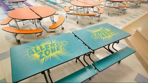 A palette of bright colors and graphics reminiscent of comic books celebrate the school's values and achievements.