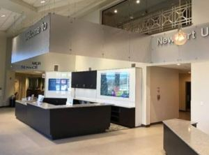 The lobby area features an interactive television display, customer service workstations and a promotional display.