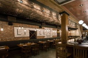 The concept for the Little Jumbo Restaurant is a 1920's New York-style speakeasy with a wooden bar, exposed brick walls, old tiles in the washrooms, and a decorative ceiling.