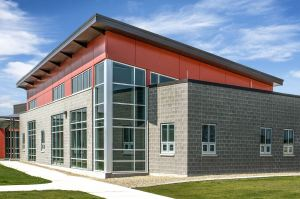 The color selection of the composite panels is driven by the colors of the existing buildings and hangars on site.