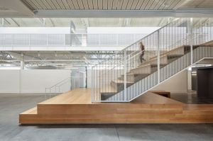 The two-story atrium is surrounded by infill railings made from a wire mesh pattern in stainless steel.
