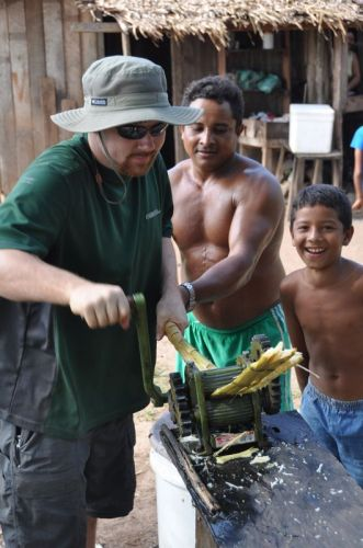 Jason takes a shot at squeezing sugar cane for a tasty, sweet drink