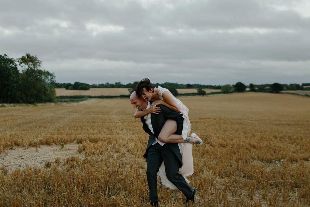 bride rides groom piggy back through farm field
