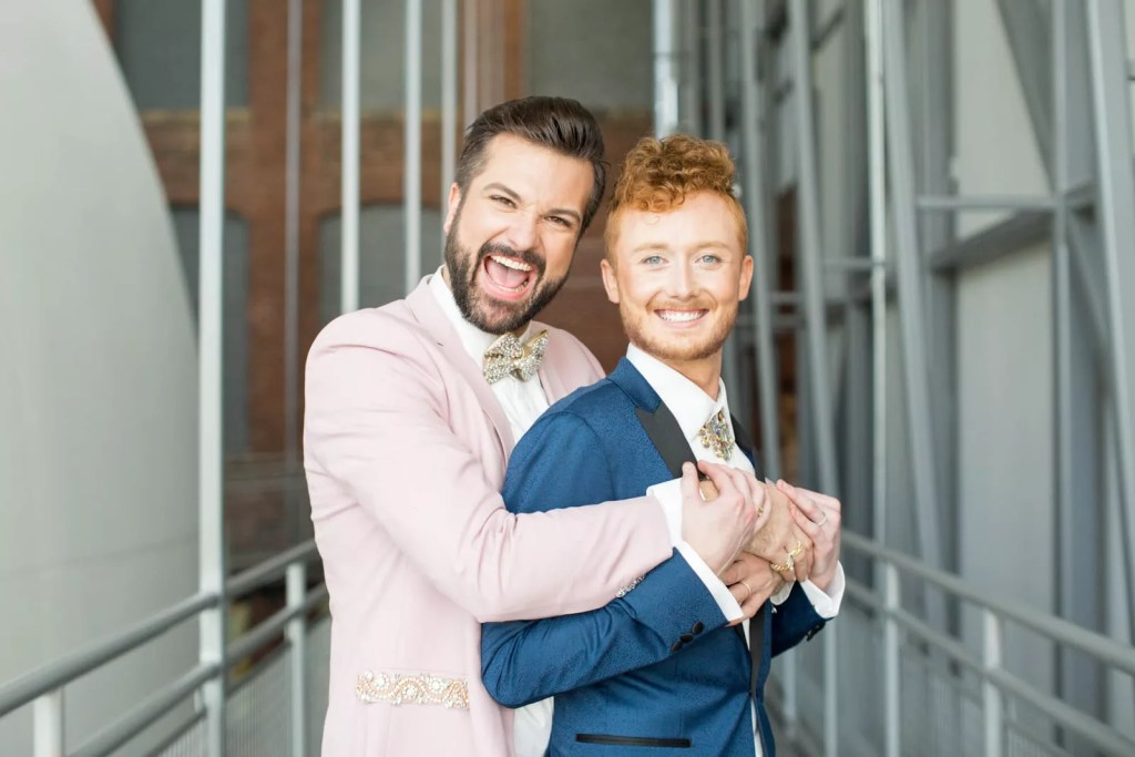 two grooms embrace smiling on their wedding day, pink suit and blue suit