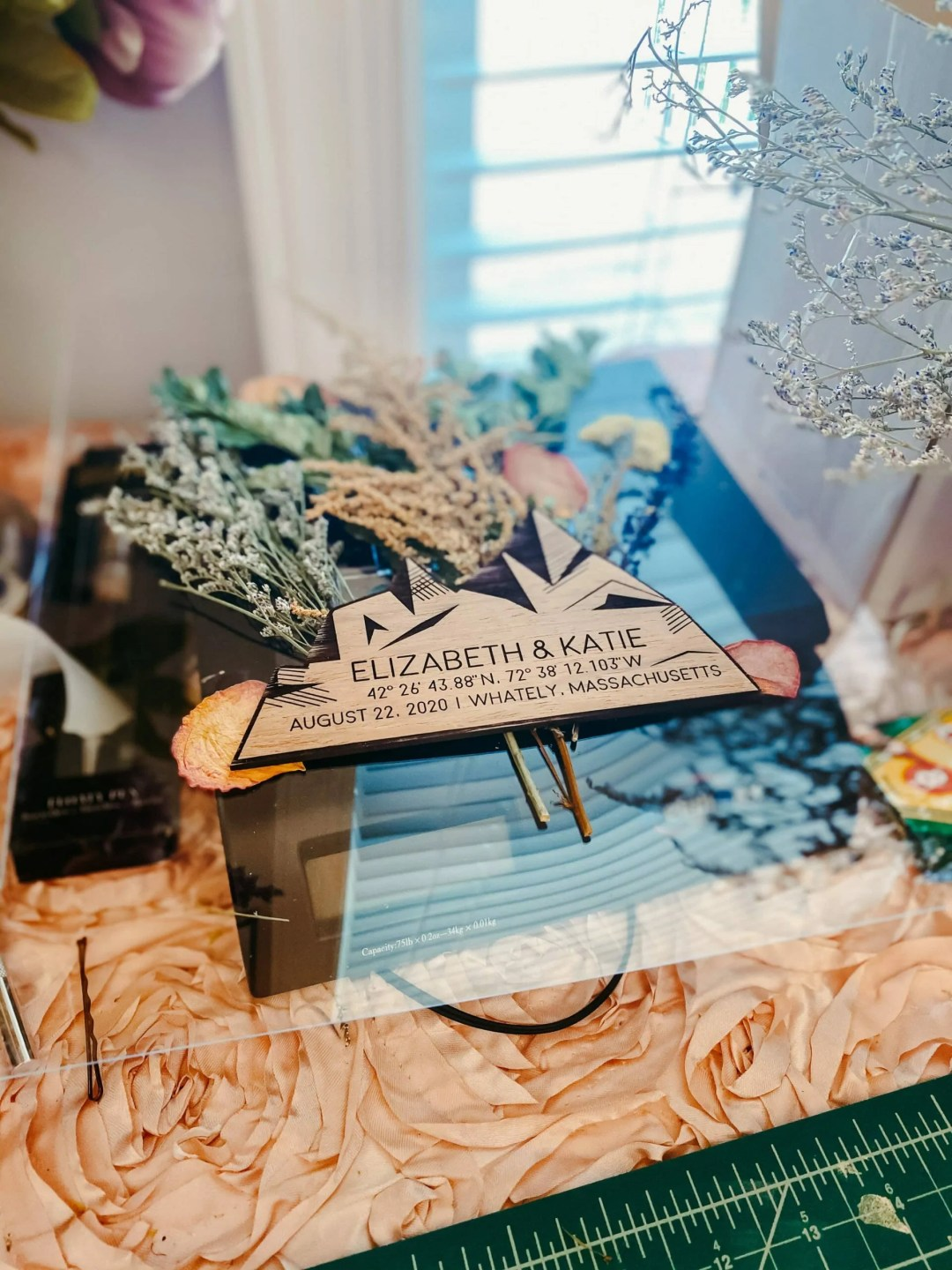 wood wedding mountain engraving sits on bed of flowers before framing