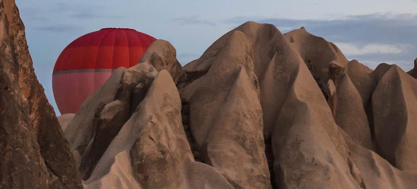 Aufsteigender Ballon hinter den Bergen