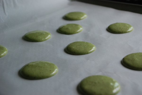 Piping matcha green tea French macarons