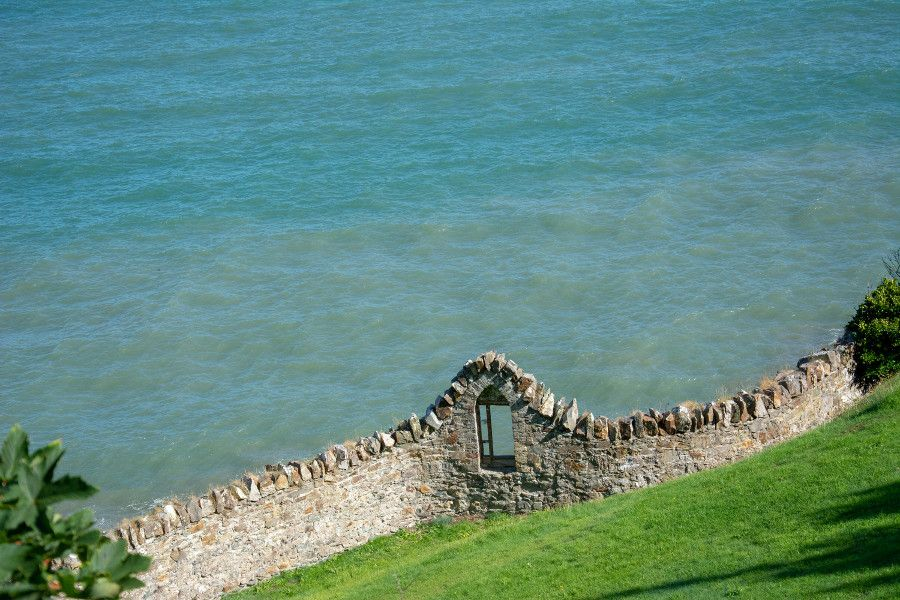 A stone wall with a window along the edge of the Irish Sea in Howth.