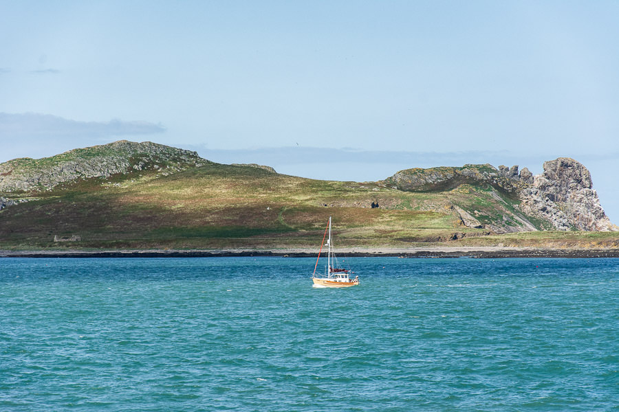 A sailboat enjoys calm waters in front of Ireland's Eye.