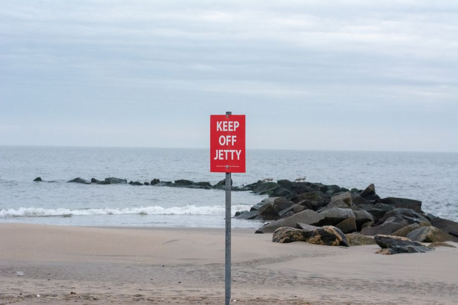 A Keep Off Jetty sign on the Coney Island beach.