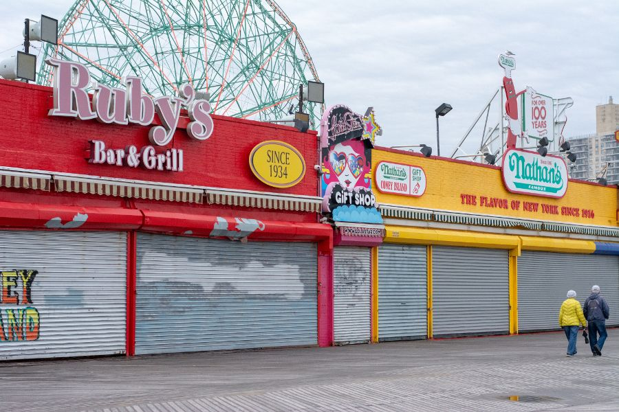A couple walking the Coney Island boardwalk near Ruby's and Nathan's Famous in winter.