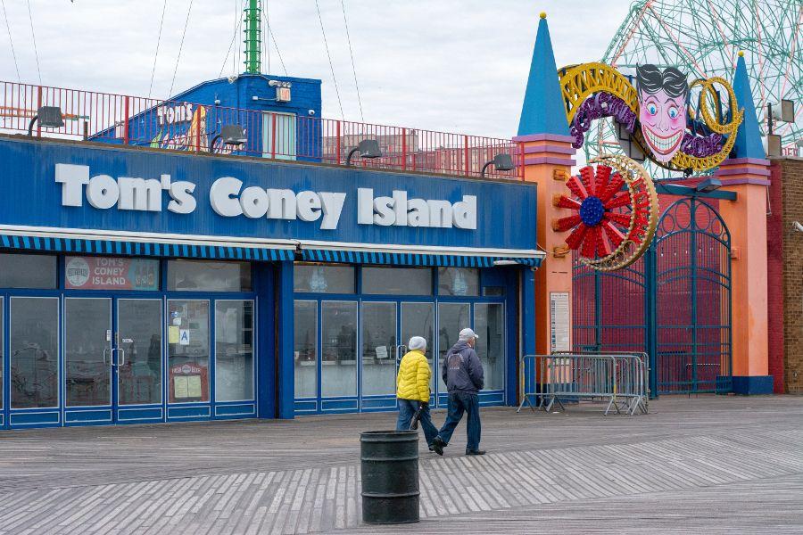 A couple walking the Coney Island boardwalk in winter.